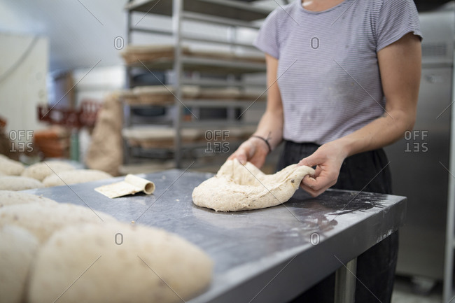 Close-up of woman preparing bread in bakery