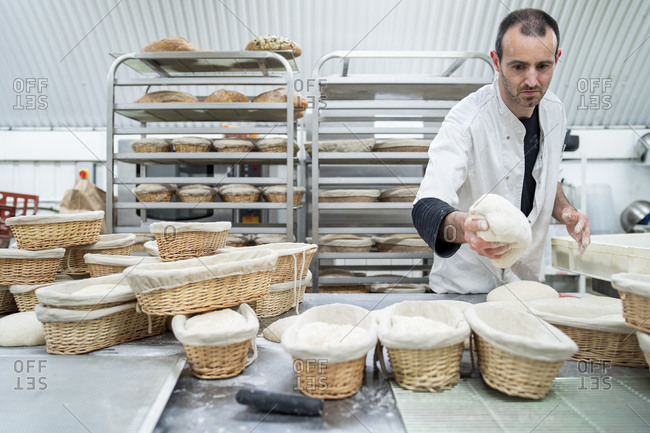Baker putting dough into basket in bakery