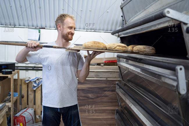 Baker baking little loaves of bread in bakery
