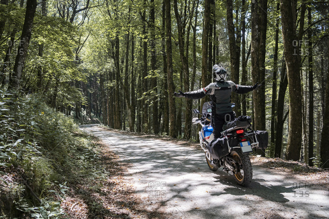 Motorcyclist on a trip on a forest road with arms outstretched