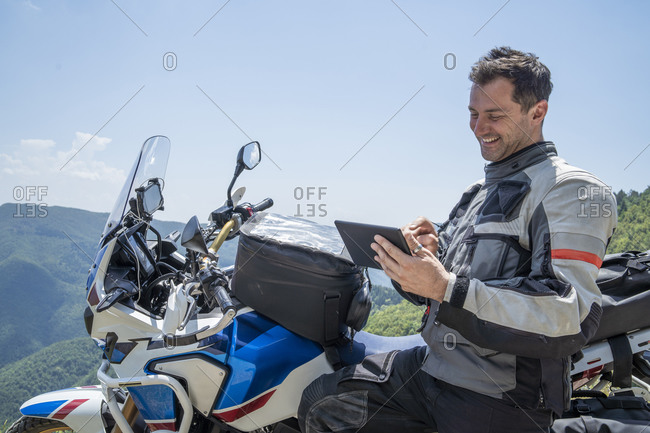 Motorcyclist on a trip having a break in the mountains using tablet- Pistoia- Tuscany- Italy