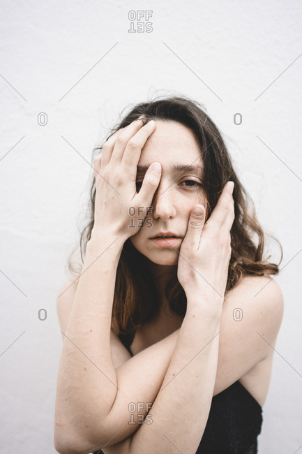Portrait of depressed young woman with hands on her face