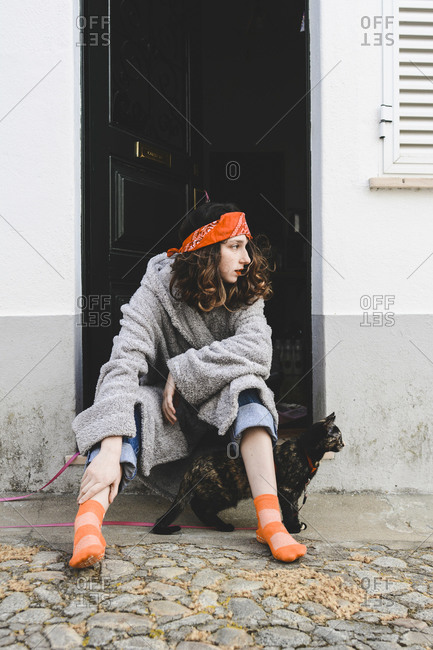 Young woman sitting in front of open entrance door with her cat looking at distance