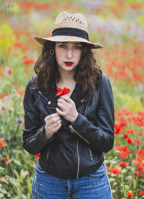 Portrait of young woman with red lips standing in poppy field