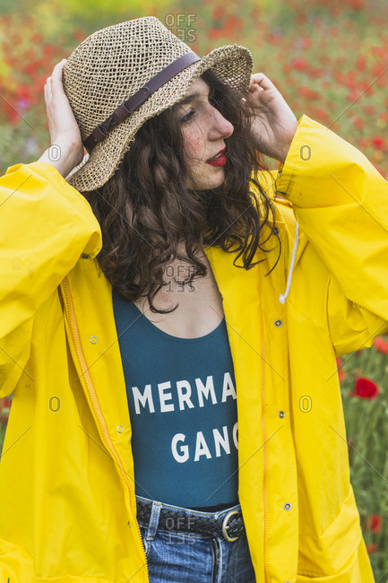 Portrait of young woman wearing hat and yellow rain jacket on flower meadow