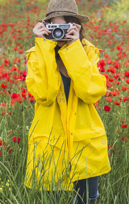 Young woman wearing yellow rain coat photographing on flower meadow with poppies