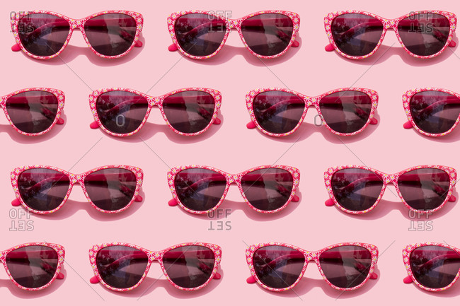 Pattern of pink retro sunglasses against pastel pink background