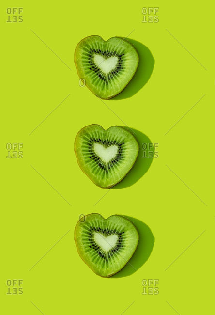 Heart shaped kiwi fruit slices pattern on green background