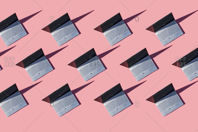 Laptop computers on pink background