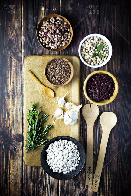 Cutting board- wooden ladles and spoon- garlic- rosemary and bowls with various beans and lentils