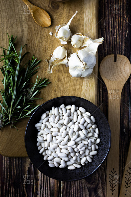 Cutting board- wooden ladle and spoon- garlic- rosemary and bowl of white beans