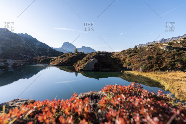 Switzerland- Canton of Grisons- Shore of Crap Alv Lajets lake at autumn sunset