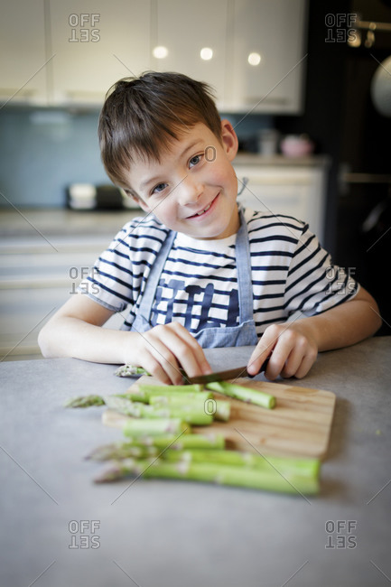 Portrait of smiling little boy cutting green asparagus in the kitchen