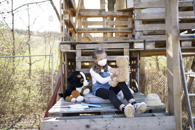 Girl with protective mask sitting in the garden at tree house and playing alone with her cuddly toys during the corona quarantine