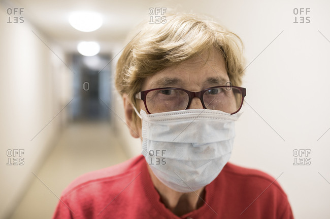 Senior woman with protective mask in corridor of retirement home