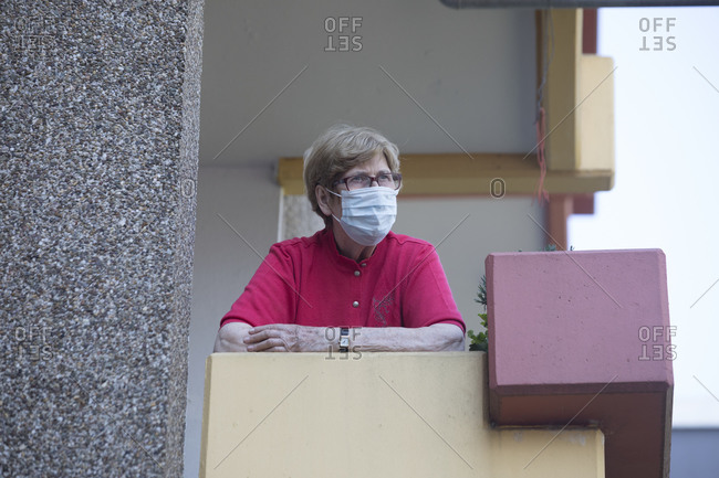 Senior woman wearing mask on balcony- retirement home