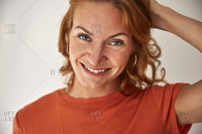 Portrait of red-haired woman- hand in hair- looking at camera