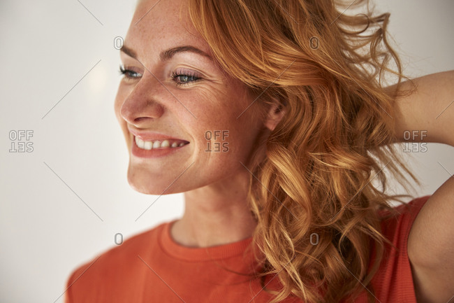Portrait of red-haired woman- hand in hair- looking sideways