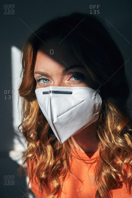Portrait of red-haired woman wearing a FFP2 mask at home