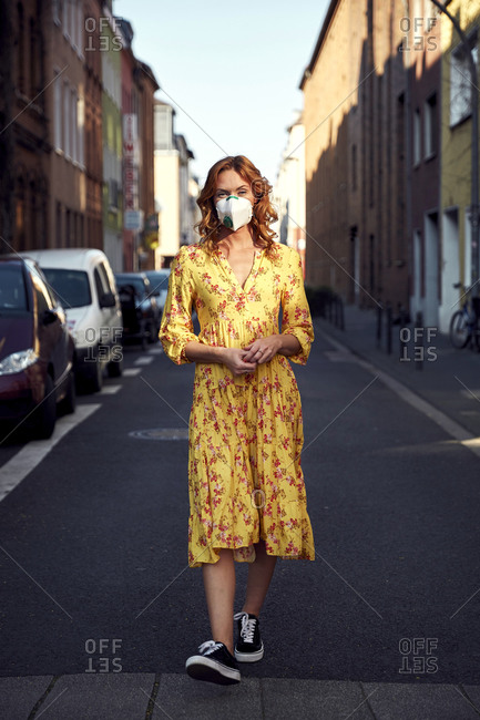 Red-haired woman wearing a FFP2 face mask and walking on empty road