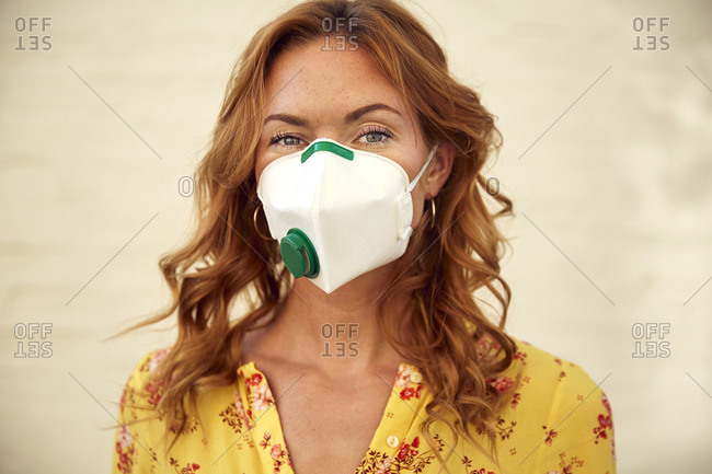 Portrait of red-haired woman wearing a FFP2 face mask in the city