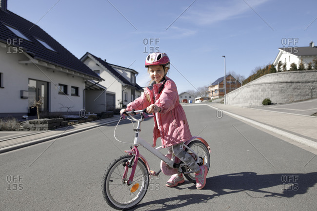 Portrait of little girl with bicycle in housing area