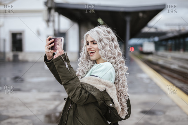 Portrait of laughing young woman taking selfie with smartphone on platform