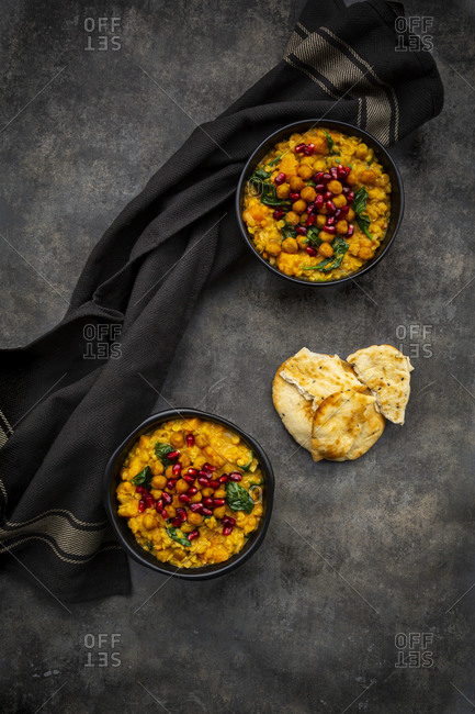 Studio shot of two bowls of vegan curry with red lentils- sweet potatoes- spinach- roasted turmeric chick-peas- pomegranate seeds- cilantro andnaan bread