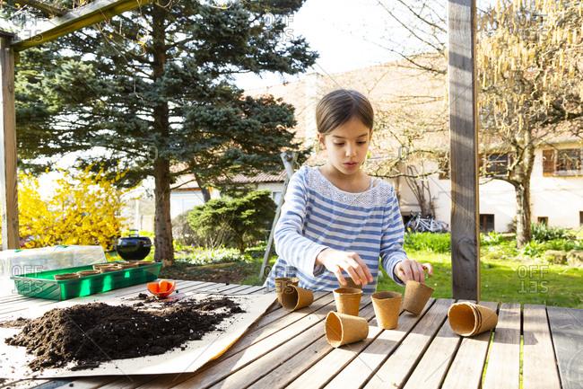 Girl filling nursery pots with soil
