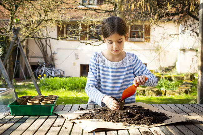 Girl filling nursery pots with soil and seeds
