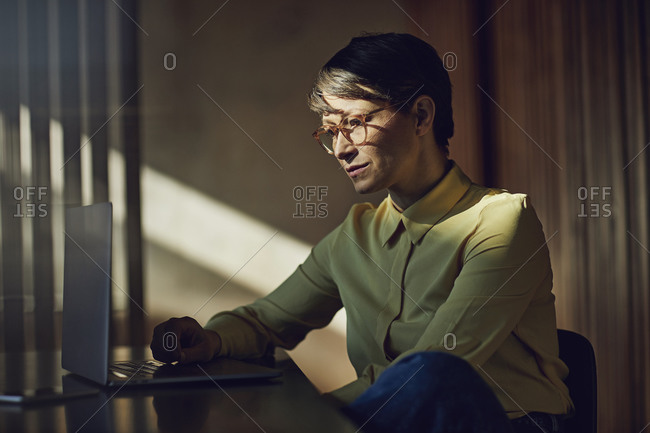 Businesswoman sitting in her sustainable office- using laptop
