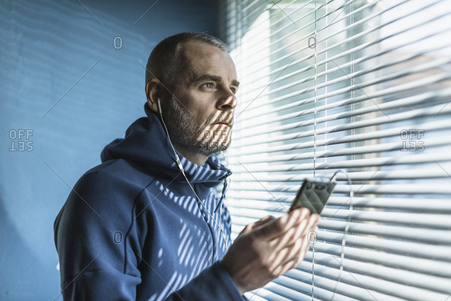 Pensive man with smartphone and earbuds looking out of venetian blind window