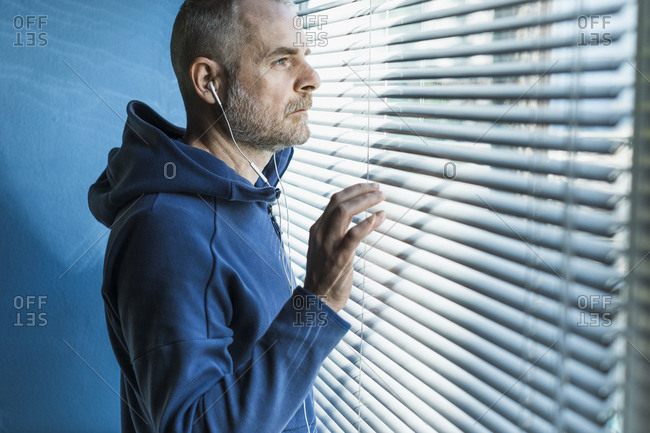 Pensive man with earbuds looking out of venetian blind window