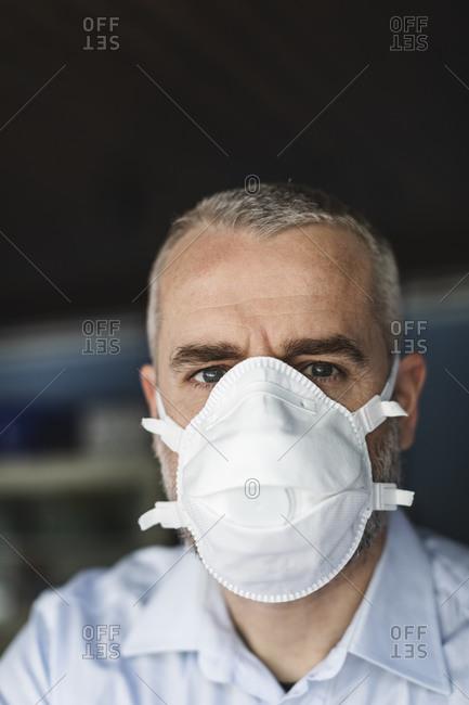 Mature man with protective mask looking at camera
