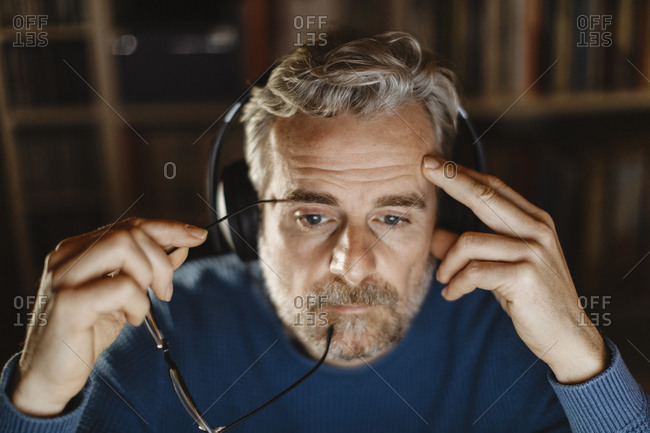 Portrait of pensive mature man with headphones in front of computer