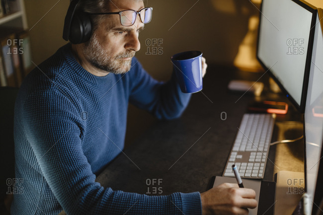 Mature man with headphones sitting at desk at home working with graphics tablet and computer