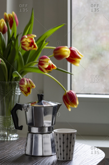 Espresso can and mug on a table with bouquet of tulips in the background