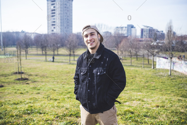 Young man standing in park- smiling- with hands in pockets