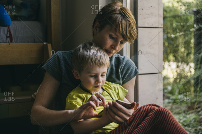 Mother and little son cuddling at home looking at smartphone