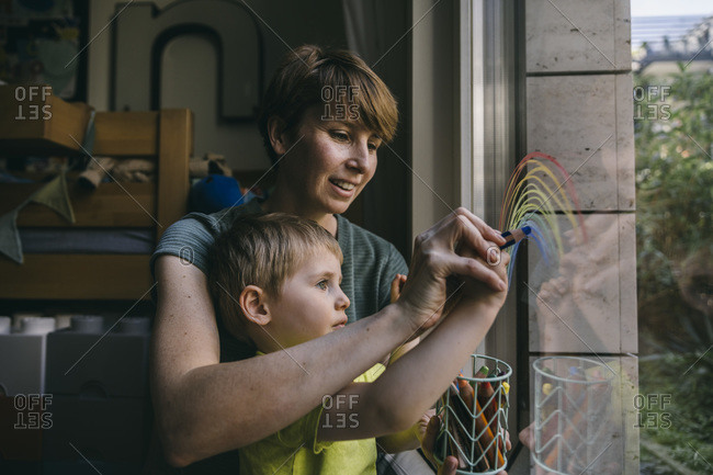 Mother and little son drawing rainbow on window at home