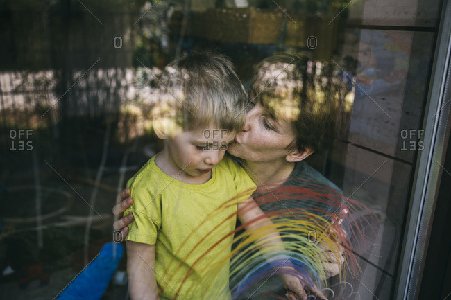 Mother kissing her little son behind window with drawn rainbow