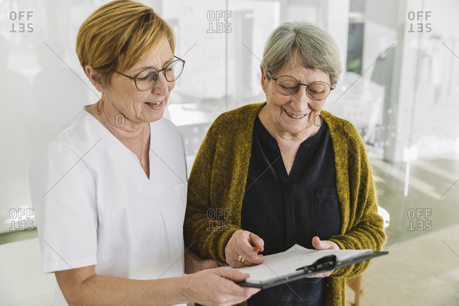 Medical secretary helping senior patient filling out document