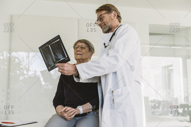 Doctor discussing x-ray image of broken hand with senior patient