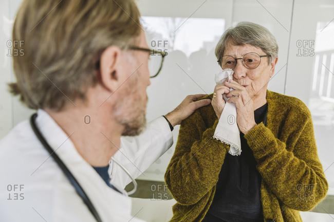 Doctor comforting sad senior patient in medical practice
