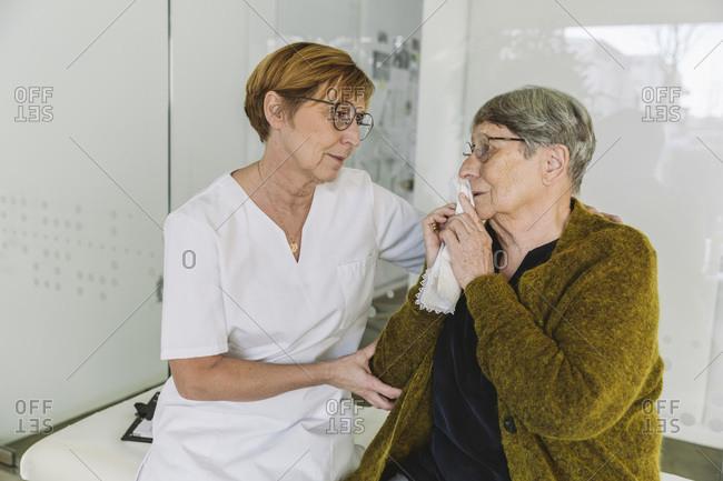 Doctor's assistant comforting sad senior patient in medical practice