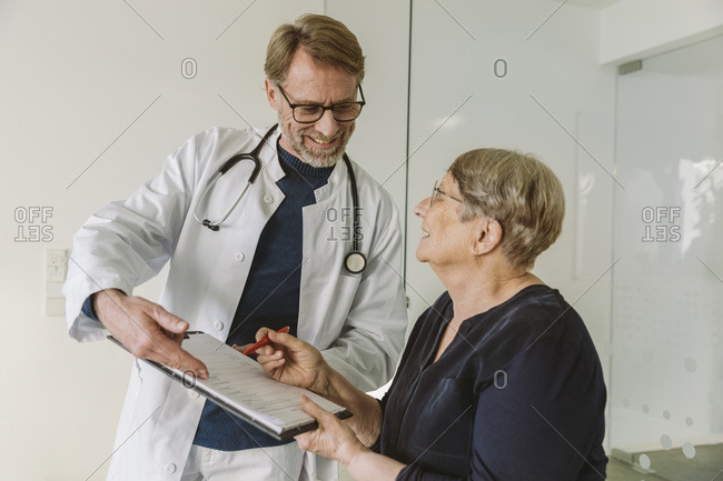 Doctor helping senior patient filling out document
