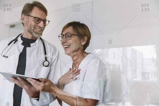 Happy doctor and assistant using tablet in medical practice