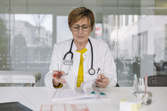 Doctor sitting at desk reviewing documents
