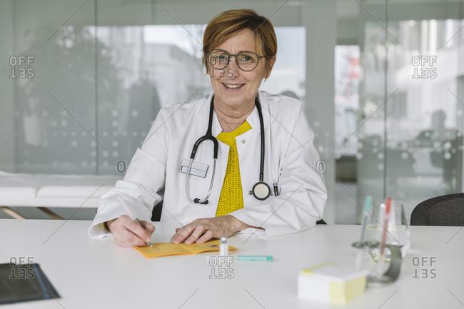 Portrait of smiling doctor filling out immunization card