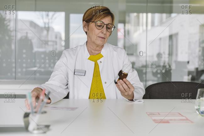 Doctor sitting at desk holding medication